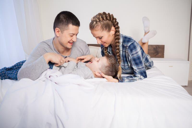 Mammafarsa och son i morgonen som hemma ligger på sängen royaltyfri bild