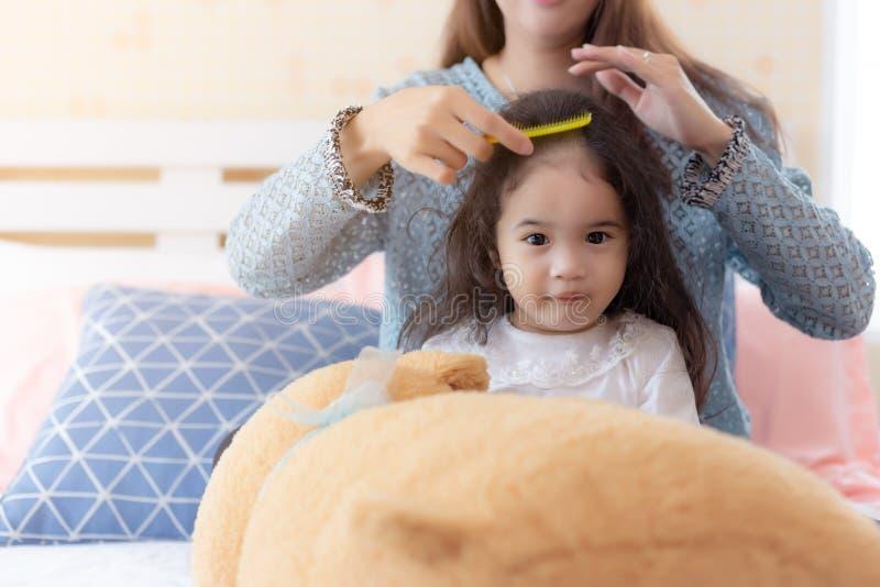 Mammahårkam hennes älskvärda lilla asiatiska dotter på säng på sovrummet Det gulliga Asien barnet är den oskyldiga flickan Lyckli royaltyfria bilder