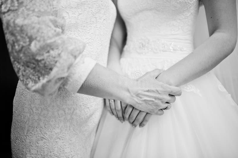 Mammahanden rymmer hennes dotterbrud på bröllopdag svart white arkivfoto