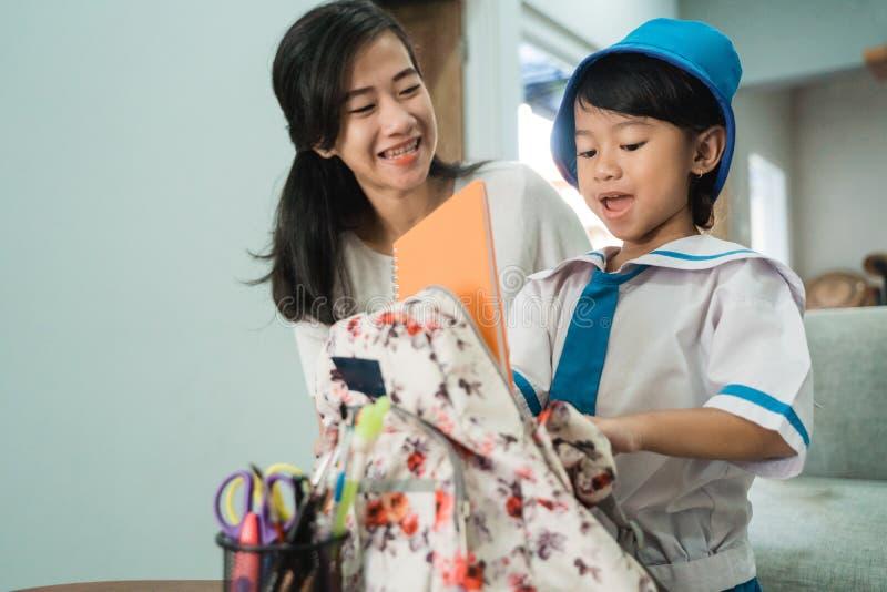 Mammahjälp hennes liten flicka som förbereder skolamaterial på hennes daughtess ryggsäck royaltyfria bilder