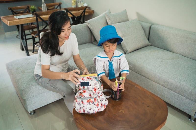 Mammahjälp hennes liten flicka som förbereder skolamaterial på hennes daughtess ryggsäck arkivfoton