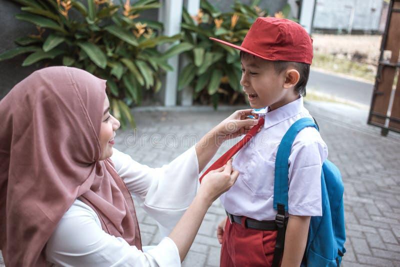 Mammahjälp hennes son som förbereder sig för skola arkivfoton