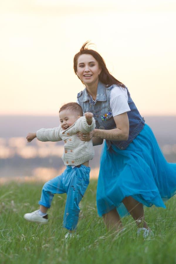 Mammakramar behandla som ett barn, och aktiviteter med honom, sommar går på fältet, molnig dag arkivfoton