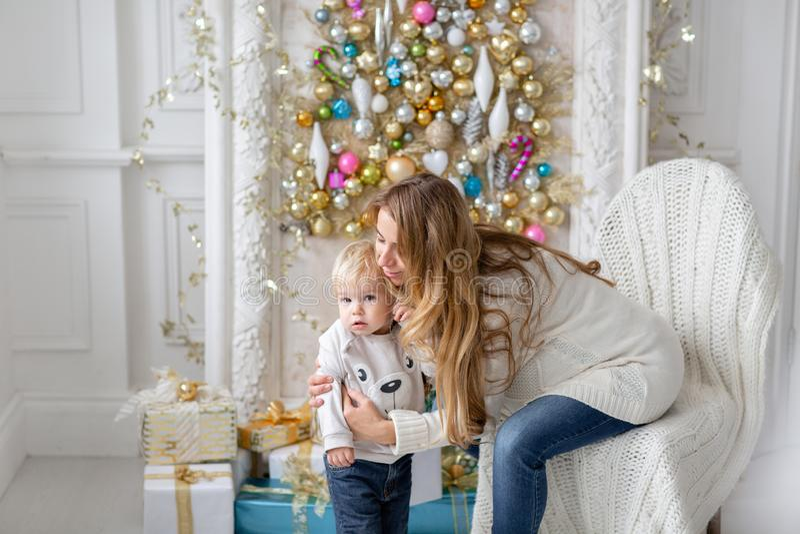 Mammalekar med barnet Lycklig familjstående i hem - omfamnar den gravida modern för barn hans lilla son lyckligt nytt år royaltyfria bilder