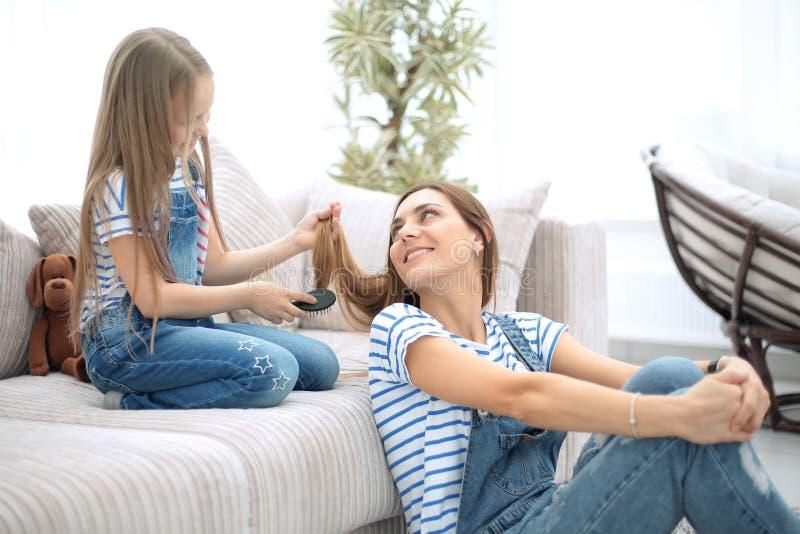 Mammalekar med hennes lilla dotter i barberaren shoppar arkivfoton