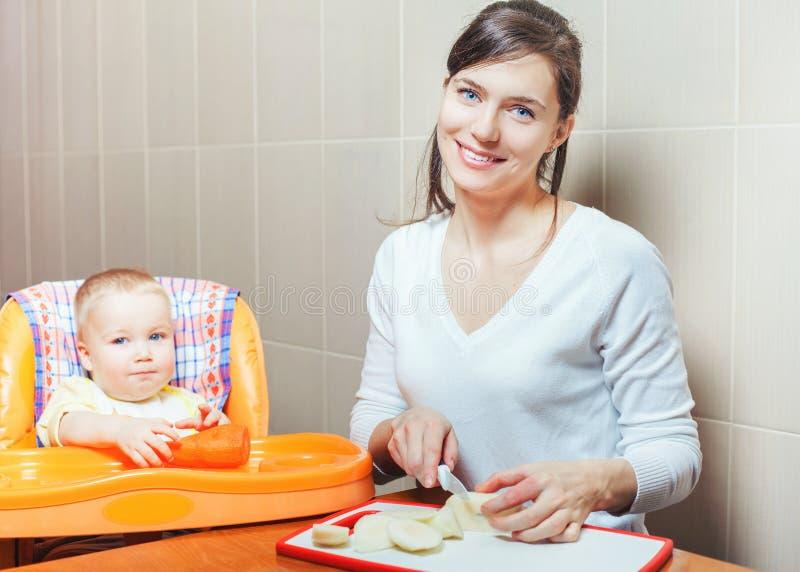 Mammamatlagning och matningar de behandla som ett barnfrukterna och grönsakerna arkivbild