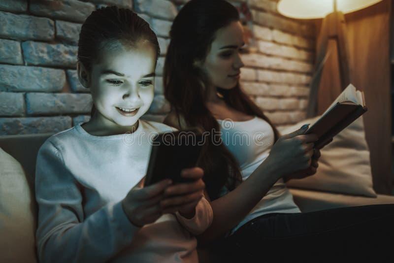 Mamman är Reades en bok, och dottern är bruk per telefonen fotografering för bildbyråer