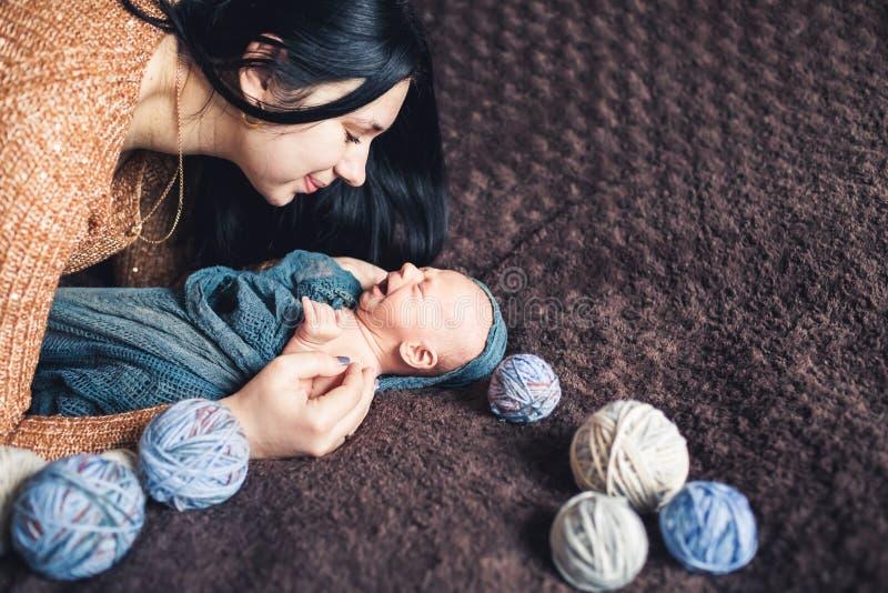 Mamman böjde till hennes nyfött behandla som ett barn och log över på honom arkivfoton