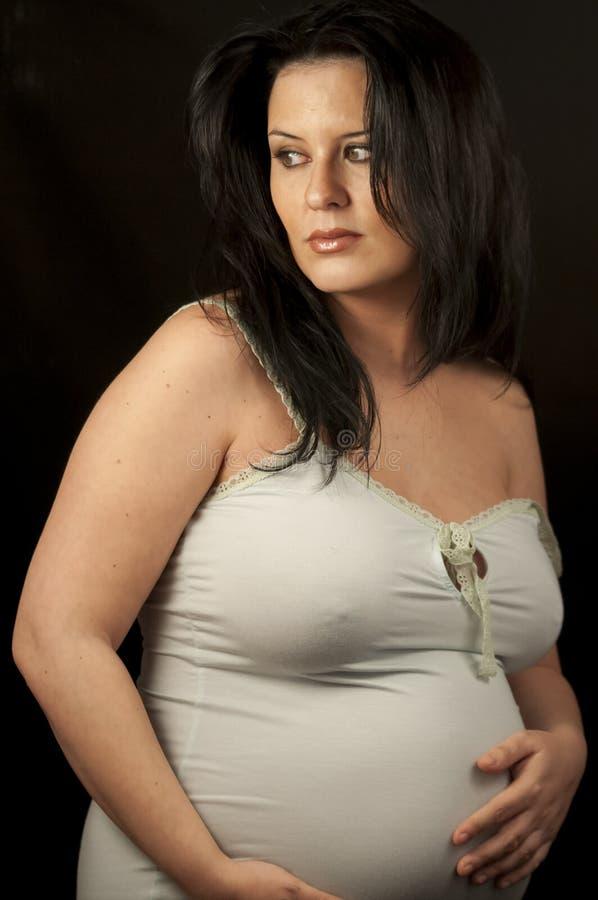 Mamman den härliga gravida brunetten i ljus beklär visningtecken royaltyfria bilder