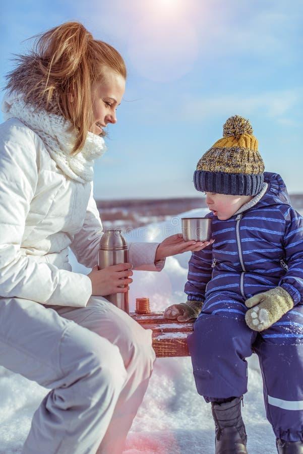 Mamman en kvinna med barnet, pojken, en son av 3 gamla år, i vintern utanför i varm kläder, sitter på en bänk, kallt varmt royaltyfri foto