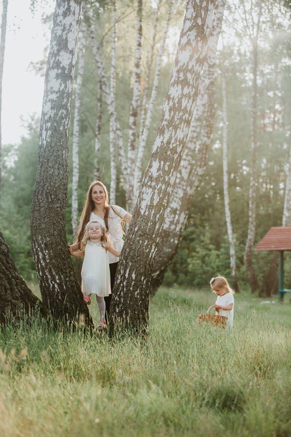 Mamman för familjfotoet med döttrar i parkerar Foto av den unga modern med två gulliga ungar utomhus i vårtid arkivfoton