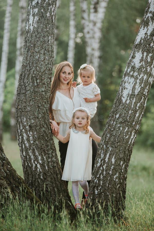 Mamman f?r familjfotoet med d?ttrar i parkerar Foto av den unga modern med tv? gulliga ungar utomhus i v?rtid arkivfoto