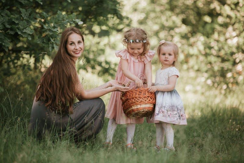 Mamman f?r familjfotoet med d?ttrar i parkerar Foto av den unga modern med tv? gulliga ungar utomhus i v?rtid royaltyfria bilder
