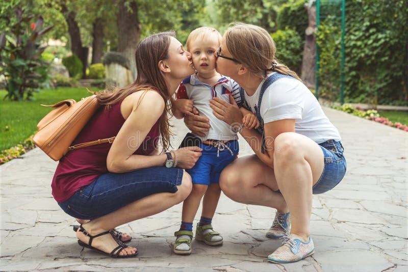 Mamman f?r tv? flickor att kyssa deras nyckfulla pysbarn i parkerar Inte en traditionell familj arkivfoto
