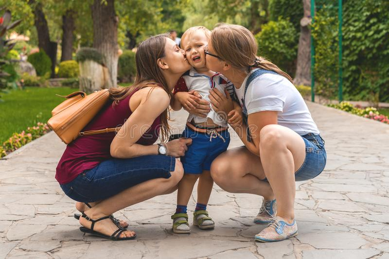 Mamman f?r tv? flickor att kyssa deras nyckfulla pysbarn i parkerar Inte en traditionell familj royaltyfri fotografi
