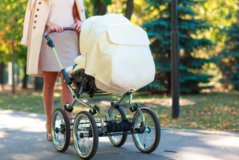 Mamman går med en sittvagn utanför royaltyfria foton