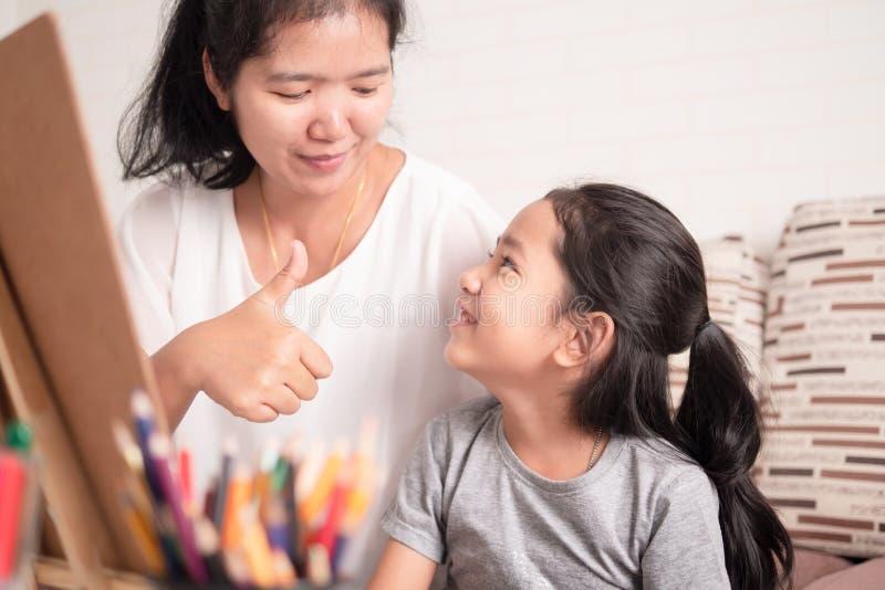 Mamman gav stora tummar-upp till hennes dotter arkivfoto