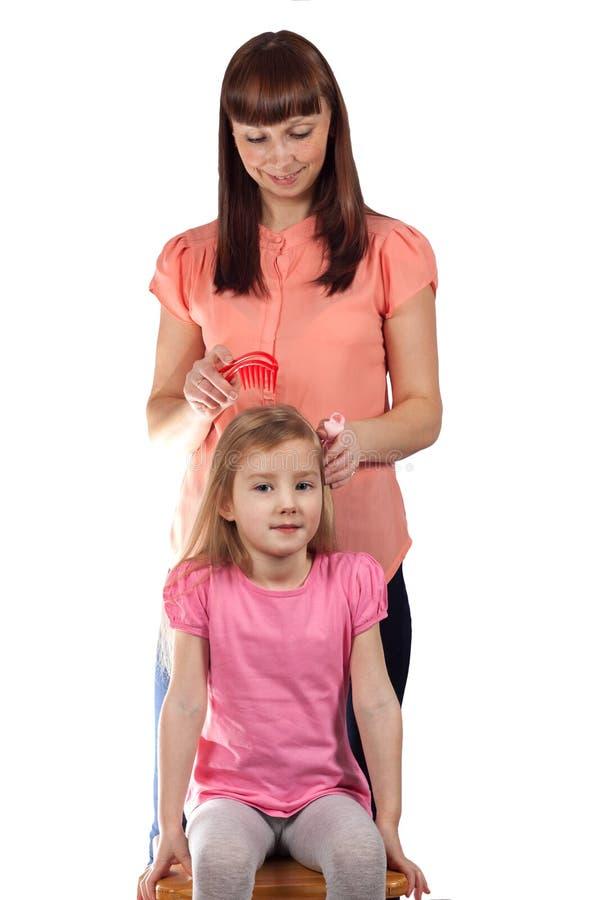 Mamman kammar hennes hår till hennes lilla dotter arkivbilder