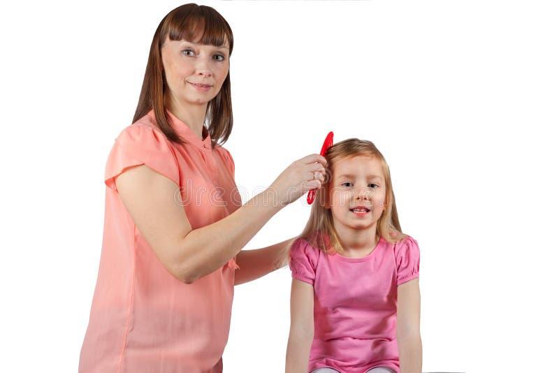 Mamman kammar hennes hår till hennes lilla dotter fotografering för bildbyråer