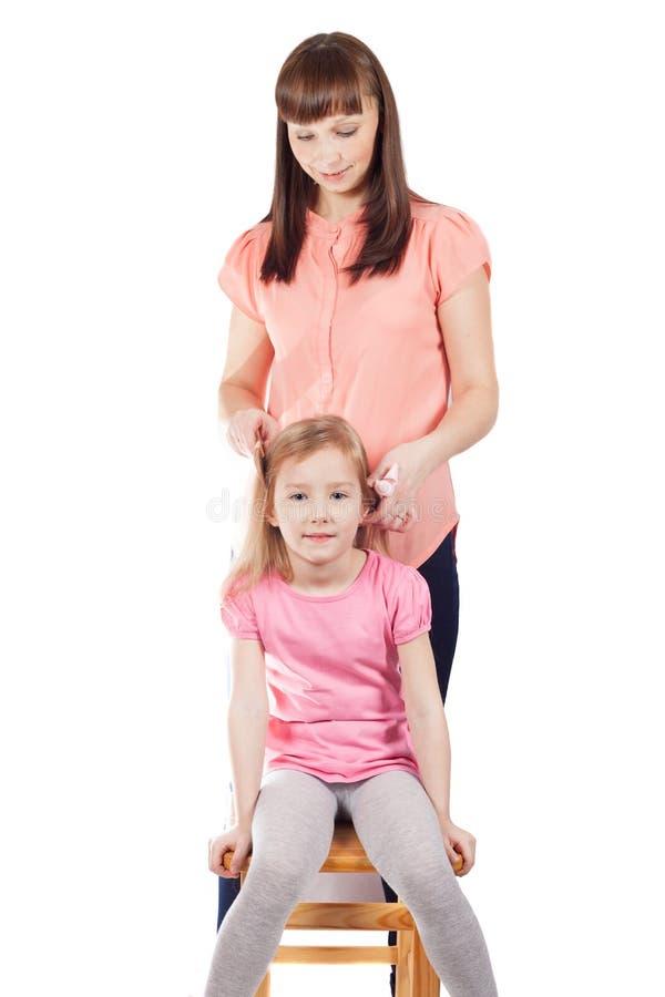 Mamman kammar hennes lilla dotter royaltyfria foton