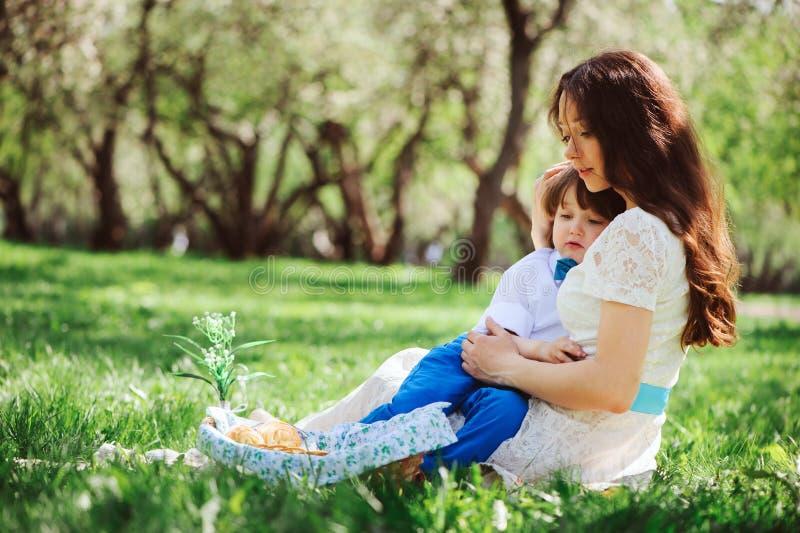 mamman kramar den ledsna litet barnsonen som är utomhus- på gå lyckligt älska för familj arkivbilder