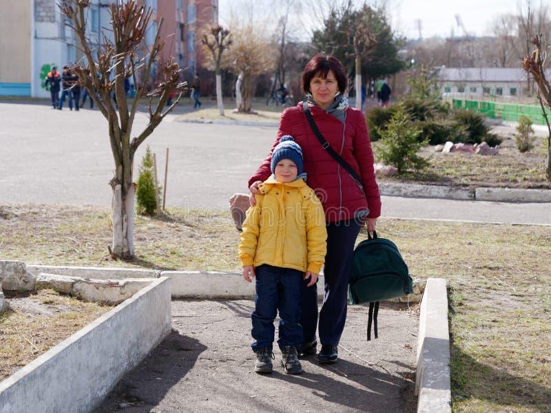 Mamman leder hennes son till grundskola för barn mellan 5 och 11 år royaltyfri fotografi