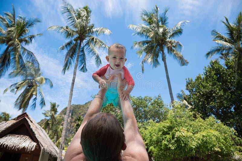 Mamman lyftte barnet i baddräkthöjdpunkt ovanför huvudet i pölen Lilla flickan är jätteglad och skrin för glädje Sommar royaltyfri fotografi