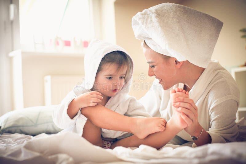 Mamman masserar mig foten Liten flicka med hennes moder efter bad royaltyfri bild