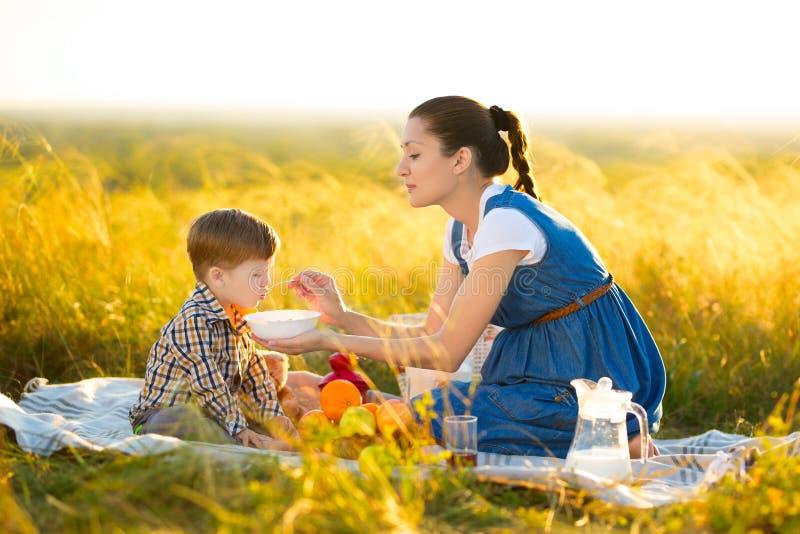 Mamman matar hennes son på en picknick Moder och barnson i solig nedgångdag Lycklig familj och sunt ätabegrepp arkivfoto