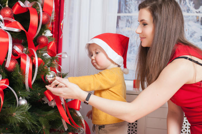 Mamman med behandla som ett barn dekorera ett julträd royaltyfri bild