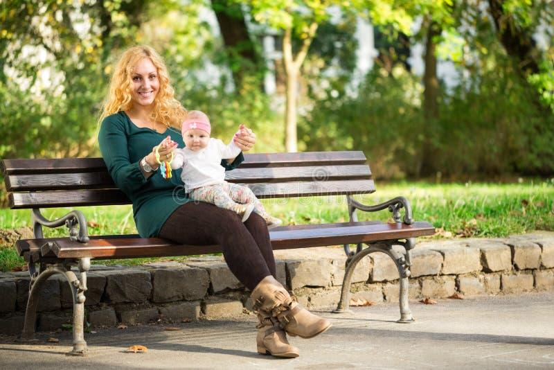 Mamman med behandla som ett barn på en parkerabänk fotografering för bildbyråer