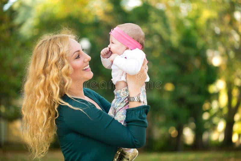 Mamman med behandla som ett barn utomhus- royaltyfri bild