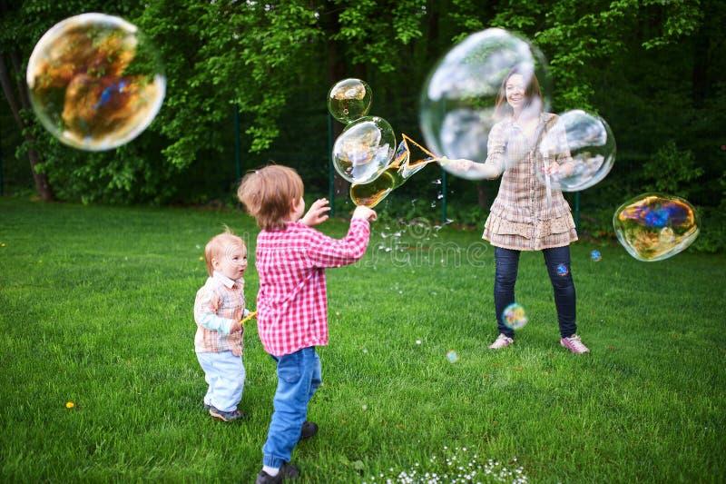 Mamman och barn som spelar s?pbubblor p? den gr?na gr?smattan i, parkerar royaltyfria bilder