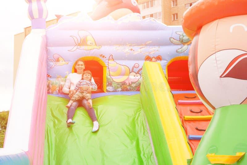 Mamman och barnet rider en glidbana i en uppblåsbar slott fotografering för bildbyråer