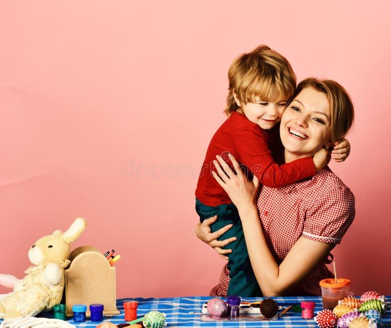 Mamman och barnet spenderar tid som gör tillsammans påskgarneringar arkivbild