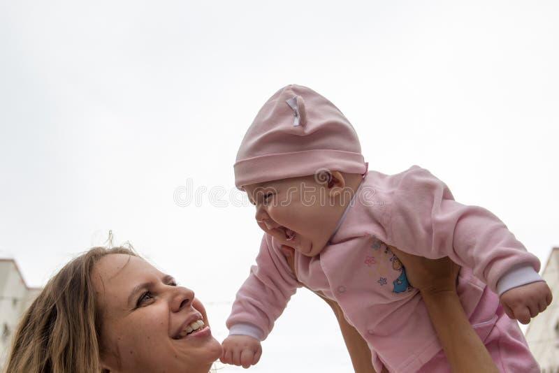 Mamman och behandla som ett barn att skratta arkivbild