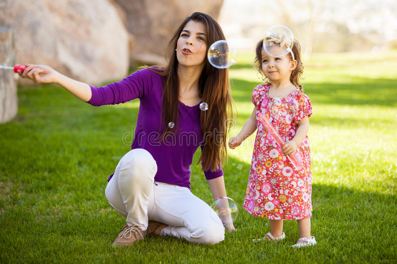 Mamman och behandla som ett barn göra några bubblor fotografering för bildbyråer
