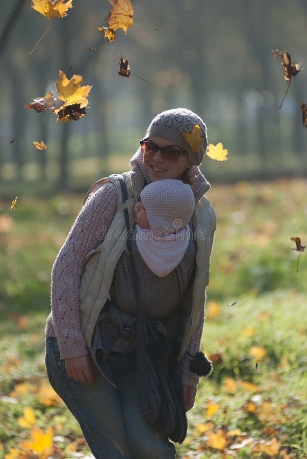 Mamman och behandla som ett barn i en rem jublar fallande höstsidor arkivfoto