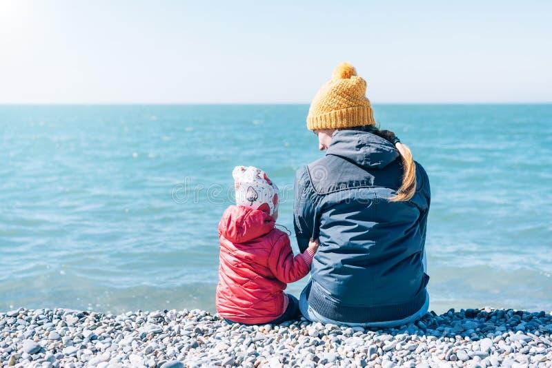Mamman och behandla som ett barn sitter på stranden arkivfoton