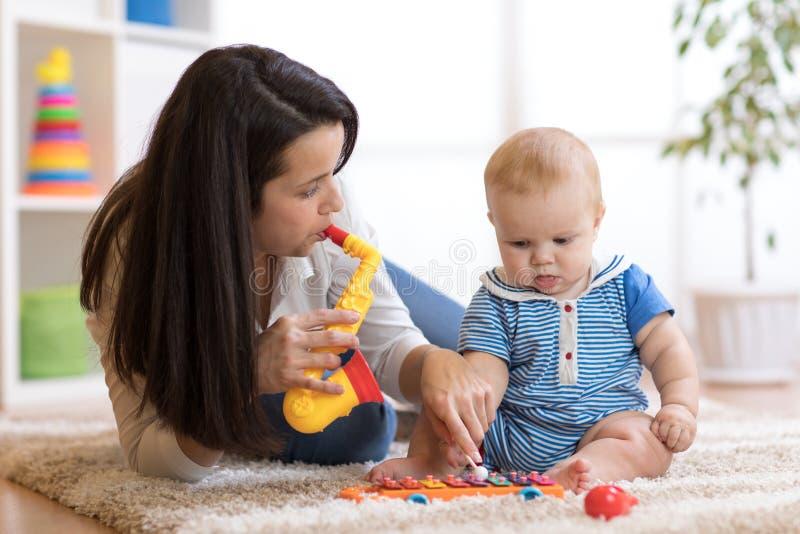 Mamman och behandla som ett barn spela musikaliska leksaker hemma fotografering för bildbyråer