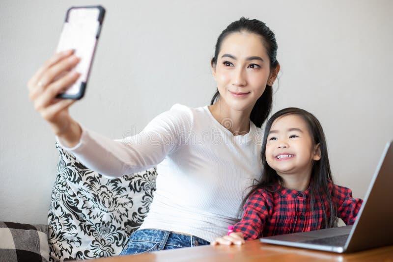 Mamman och döttrar tar selfies och att skratta och att le som är lyckligt arkivfoton