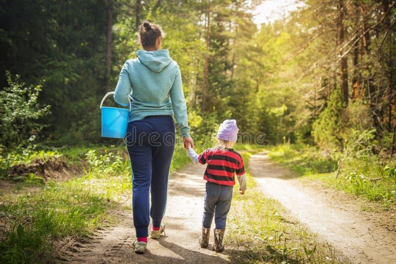 Mamman och den lilla dottern går på vägen i höstskogen som familjhopsamlingen plocka svamp och bär i skogen royaltyfria foton