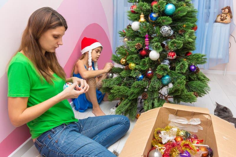 Mamman och dottern dekorerar julgranen arkivbild