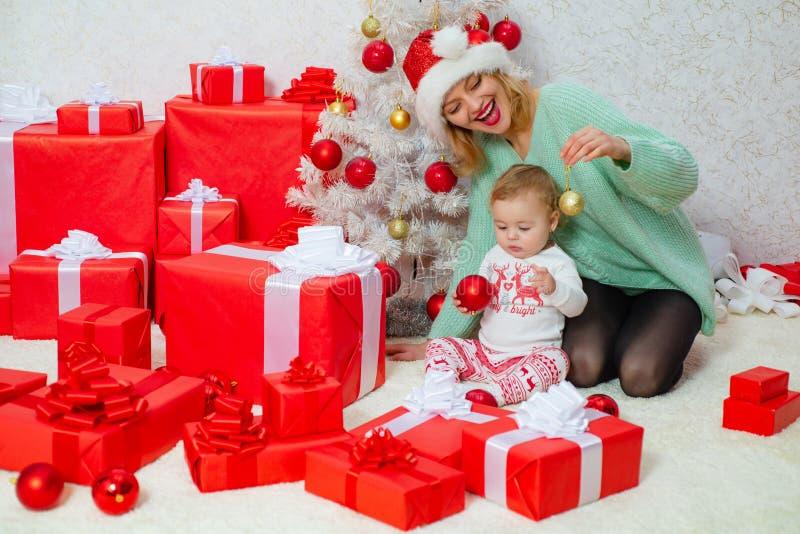 Mamman och dottern dekorerar julgranen Jul som älskar familjen Berömferie och samhörighetskänsla nära träd royaltyfria foton
