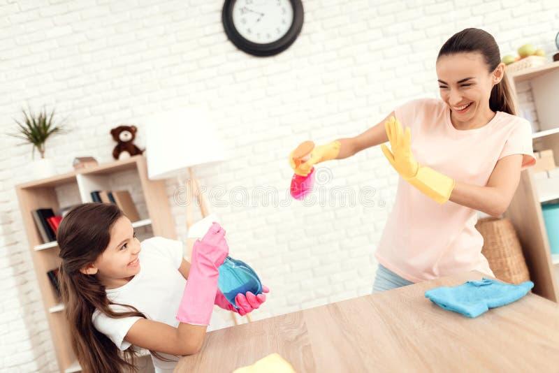 Mamman och dottern gör ren hemma fotografering för bildbyråer
