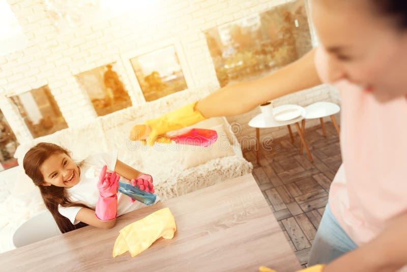 Mamman och dottern gör ren hemma De står bredvid den äta middag tabellen och bedrar omkring royaltyfri bild