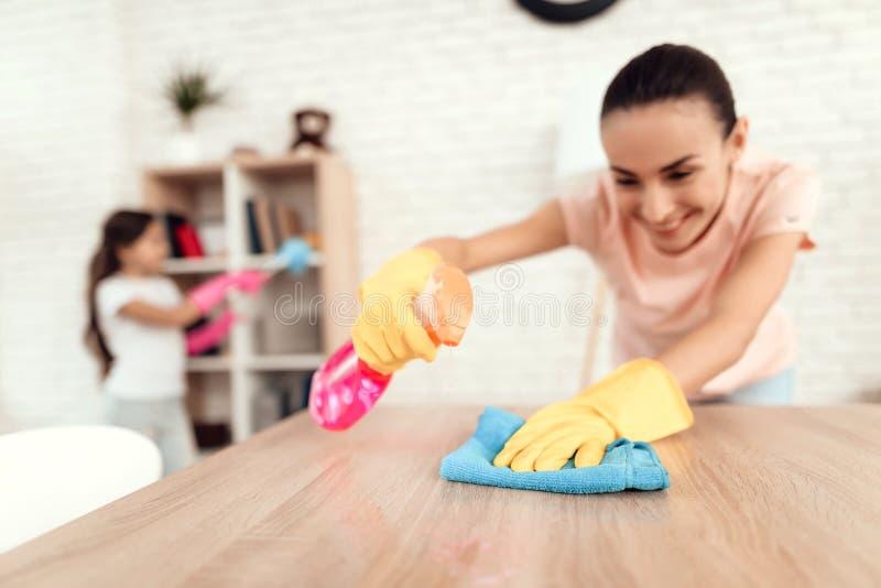 Mamman och dottern gör ren hemma Torka hyllorna och tabellen arkivfoton