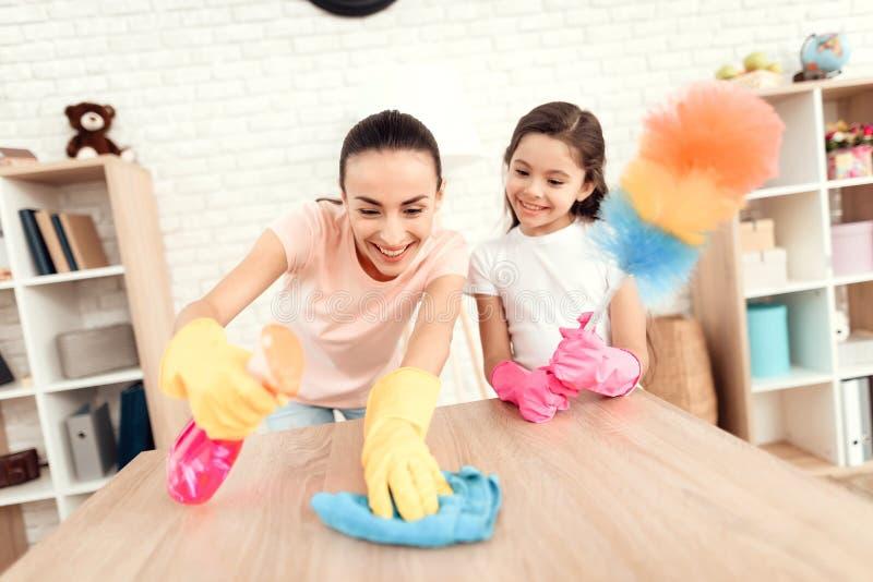 Mamman och dottern gör ren hemma Torka hyllorna och tabellen royaltyfria foton