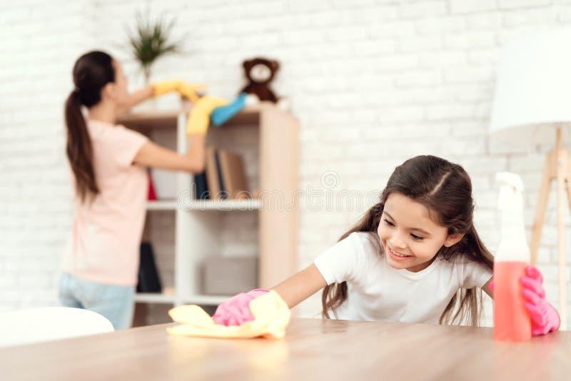 Mamman och dottern gör ren hemma Torka hyllorna och tabellen royaltyfri bild