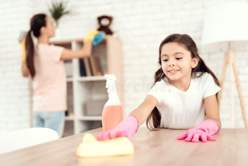 Mamman och dottern gör ren hemma Torka hyllorna och tabellen fotografering för bildbyråer